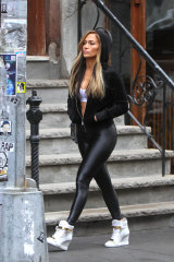 Jennifer Lopez, seen filming Hustlers in March, wearing both activewear and some throwback wedge sneakers.