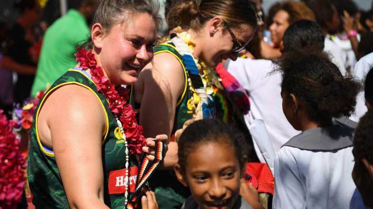 Cult hero: Rhiannon Revell-Blair (left) is mobbed by students as the Jillaroos visited Wardstrip Demonstration Primary School in Papua New Guinea.