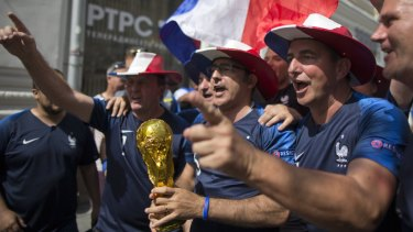 Expectant: French fans with a model World Cup in the streets of Moscow.