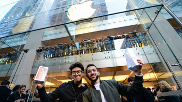 Sydney student Teddy Lee and Mazen Kourouche (right) hold up their prizes after being first in line for new iPhones.