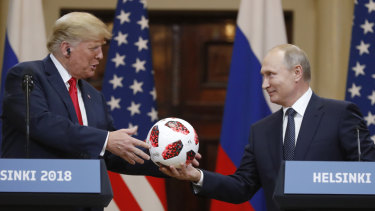 President Vladimir Putin gives a soccer ball to US President Donald Trump during their press conference on Monday.