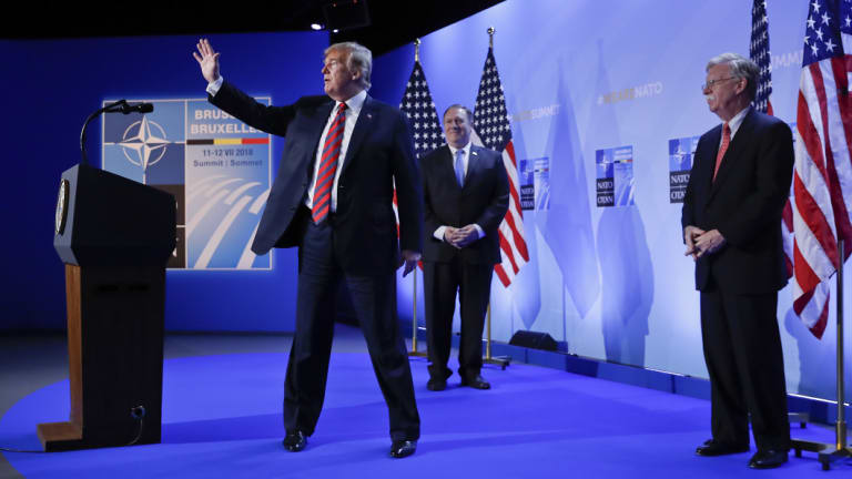 Trump, with Secretary of State Mike Pompeo and National security adviser John Bolton, waves as he walks off stage.