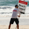 A Gold Coast lifeguard erects the beach closed sign.