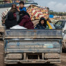 Displaced Syrian families ride in the back of a truck loaded with families' possessions in Idlib, Syria.
