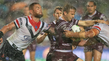Downpour: Manly's Kane Elgey is tackled in the big wet.