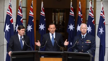 Then-prime minister Tony Abbott in 2015 announcing preparation for a troop deployment to Iraq. He is joined by then-Defence Minister Kevin Andrews and former Defence Force chief Air Chief Marshal Mark Binskin, and a number of national flags.