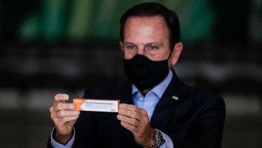 Governor of Sao Paulo Joao Doria holds a box of the trial CoronaVac vaccine by China's Sinovac last year.