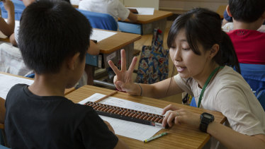 Third-graders learning how to use an abacus during maths class at Daini Zuiko Elementary School in Tokyo.