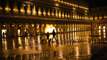 Tourists pull their trolleys as they walk through a nearly empty St Mark's Square on a rainy day in Venice.