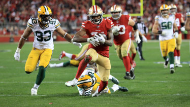 Raheem Mostert beats a tackler to score one of his four touchdowns in the NFC Championship game against the Packers.