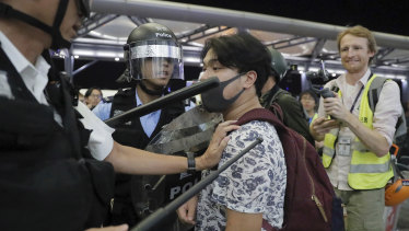 Police officers in riot gear arrest a protester at Hong Kong Airport.