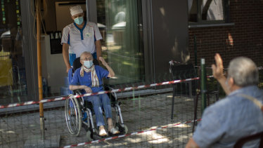 Liliana Van Dyck, 85, says goodbye to her son, Marc, at the end of his visit during a partial lockdown at the Les Jardin D'astrid rest home in Maurage, Belgium.
