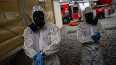 Military personnel, wearing full protective equipment, clean their hands after disinfecting an ambulance used to carry a coronavirus COVID-19 patient in Brussels.