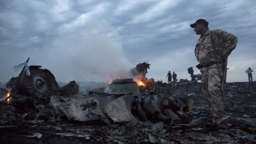 People walk among the debris of MH17 where pieces of it crashed to the ground near the village of Hrabove in Ukraine.