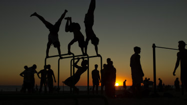 Men exercise in a public gym as the sun sets at the Victoria beach in Cadiz, Spain.