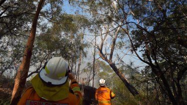 Captain Craig Byrne (right) from the Grays Point Rural Fire Service with his crew watch water bombing as they monitor a fire in bushland off Windle Place in Menai, Sydney.