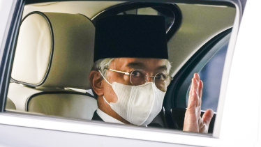 Malaysia's King Sultan Abdullah Sultan Ahmad Shah waves as he leaves National Palace in Kuala Lumpur on Sunday.