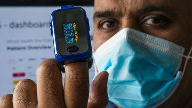 Associate Professor Joseph Mathew, an emergency physician at The Alfred Hospital, measures his oxygen levels.