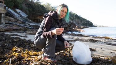 Artist Marina DeBris collects plastic straws from the oceanside.