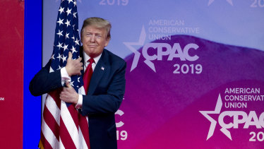 US President Donald Trump hugs the American flag at the Conservative Political Action Conference in Maryland earlier this year.