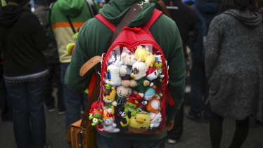 An attendee wears a backpack full of mascots at the Yuru-chara Grand Prix in Nagano, Japan.