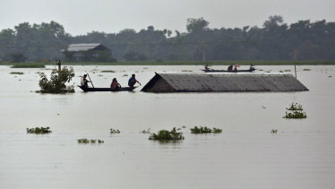 Flood affected villagers travel on boats near a submerged house in Burha Burhi village, east of Gauhati, India.