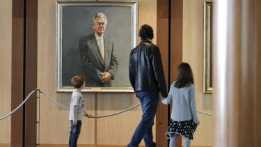 Brisbane's Bernard Macnaught and his children Thomas and Victoria view former prime minister Bob Hawke's portrait during their visit to Parliament House on Wednesday.