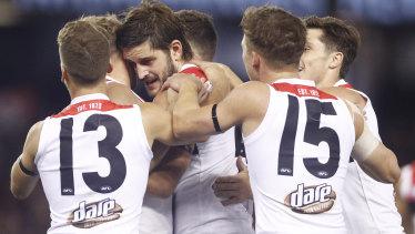 Saint Josh Bruce (centre) celebrates a goal.