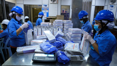 Employees pack latex gloves into boxes at a Top Glove Corp. factory in Selangor, Malaysia. It's been a good year for glove companies and their founders.
