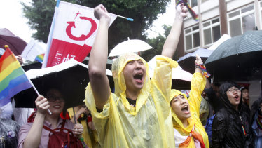 Same-sex marriage supporters cheer outside Parliament in the rain.