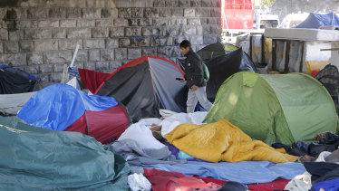 An afghan migrant walk trough a makeshift camp in Paris.