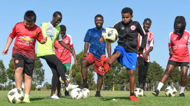 Eangano Singehebhuye teaches children to player soccer in a park in St Albans.