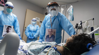 Medical staff wear their photos outside their PPE while checking on a patient at a COVID-19 intensive care unit in Houston, Texas.