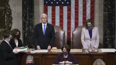 Former vice-president Mike Pence is pictured with Speaker of the House Nancy Pelosi just before being ushered out of the chamber on January 6.