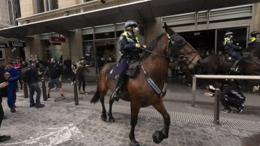 Mounted police are pelted with bottle and flower pots during the anti-lockdown protest in Sydney.