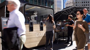 A robotic arm serves up coffee at Cafe X's downtown San Francisco kiosk.