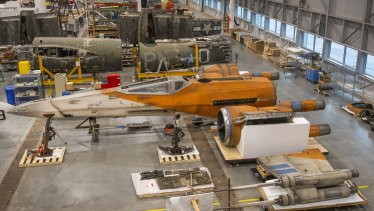 A Star Wars X-wing fighter is being constructed and conserved next to a World War II-era air plane in the Smithsonian's restoration hangar.