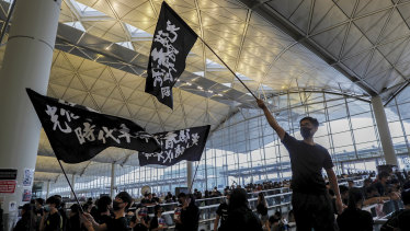 Protesters wave flags at the Hong Kong International Airport.