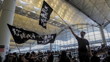 Protesters wave flags at the Hong Kong International Airport.