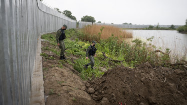 Enhancing the human oversight: police officers patrol alongside a steel wall at Evros river, near the village of Poros, at the Greek -Turkish border.