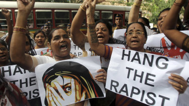 Indian activists hold placards demanding rapists be hanged.