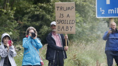 People hold posters when watching the motorcade vehicles transporting Donald Trump and First Lady Melania Trump, on the road leaving Trump Turnberry golf resort, Scotland.