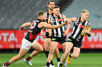 Collingwood's Jordan De Goey breaks through a tackle by Jake Stringer.