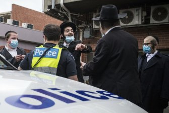 A young man argues with police outside a synagogue in Ripponlea, in Melbourne's south-east, last week.