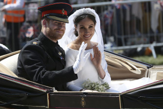 Prince Harry and Meghan ride in an open-topped carriage after their wedding ceremony in May 2018.