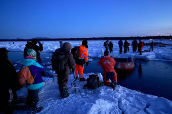 Rescuers in the foreground help a group of stranded fishermen.