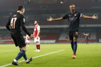 Phil Foden (left) celebrates with teammate Fernandinho after scoring City's third goal.