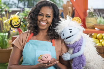 """Thinking of knitting and retirement: Michelle Obama, former US first lady, with characters from the Netflix series """"Waffles + Mochi"""""""