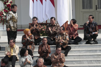 Subianto stands as he is introduced by his former rival, Widodo (right).