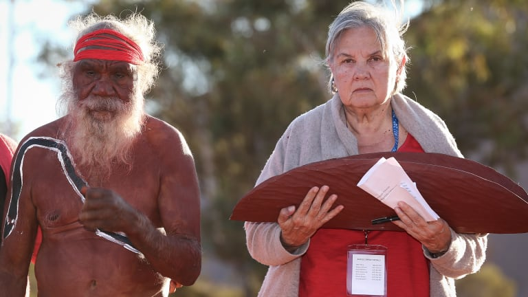 Mutitjulu elder Rolley Mintuma joins Pat Anderson as she carries the Uluru Statement from the Heart last year.